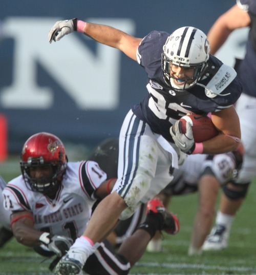 Rick Egan   |  The Salt Lake Tribune  Brayan Kiraya, runs for the Cougars,  in football action, BYU vs. San Diego State, at Lavell Edwards Stadium in Provo,  Saturday, October 9, 2010  Brandon Davis (11) defends for the Aztecs.