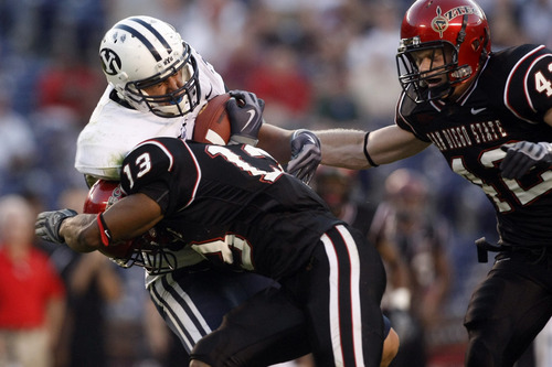 Photo by Chris Detrick  |  The Salt Lake Tribune  Brigham Young's Dennis Pitta #32 makes a catch past San Diego State's Brandon Davis #13 and San Diego State's Nick Sandford #42 during the second half of the game at Qualcomm Stadium Saturday October 17, 2009. BYU won the game 38-28.