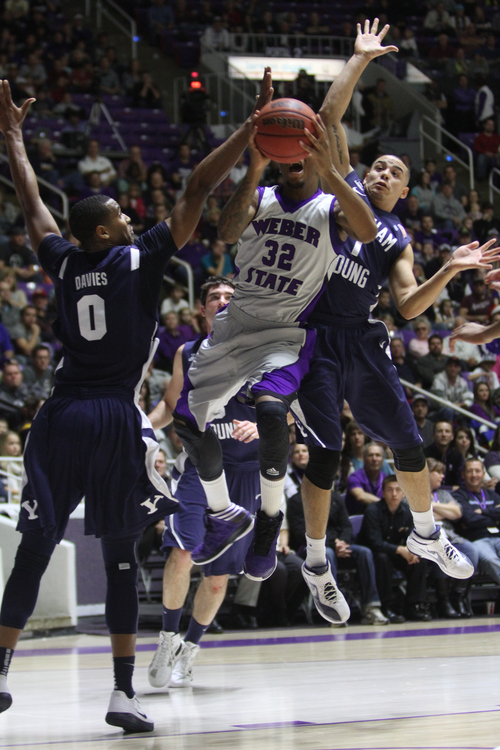 Rick Egan    The Salt Lake Tribune   Weber State Wildcats guard/forward Royce Williams (32) drives to the hoop between Brigham Young Cougars forward Brandon Davies (0) and Brigham Young Cougars guard Raul Delgado (1) in basketball action, BYU vs. Weber State, in Ogden, Saturday, December 15, 2012.