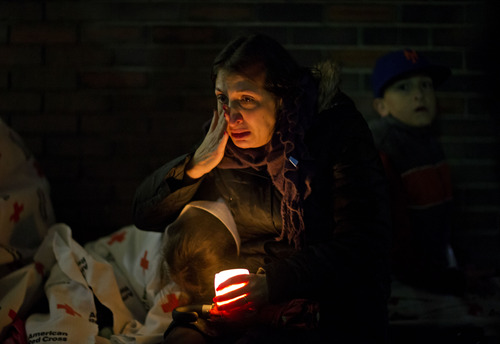 A mourner weeps while listening to President Barack Obama speak on a loudspeaker while sitting outside a memorial at Newtown High School for the victims of the Sandy Hook Elementary School shooting, Sunday, Dec. 16, 2012, in Newtown, Conn. (AP Photo/David Goldman)