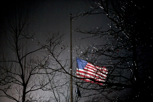 A U.S. flag flies at half staff outside the  Newtown High School before President Barack Obama is scheduled to attend a memorial for the victims of the Sandy Hook Elementary School shooting, Sunday, Dec. 16, 2012, in Newtown, Conn. A gunman walked into Sandy Hook Elementary School in Newtown Friday and opened fire, killing 26 people, including 20 children. (AP Photo/David Goldman)