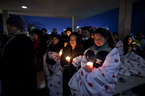Residents hold a candlelight vigil outside Newtown High School after President Barack Obama delivered remarks at an interfaith vigil for the victims of the Sandy Hook Elementary School shooting on Sunday, Dec. 16, 2012, at Newtown High School in Newtown, Conn. A gunman walked into the elementary school Friday and opened fire, killing 26 people, including 20 children. (AP Photo/ Evan Vucci)