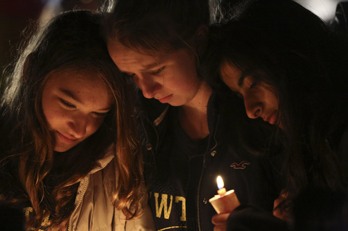 Kate Suba, left, Jaden Albrecht, center, and Simran Chand pay their respects at one of the makeshift memorials in honor of the victims of the Sandy Hook Elementary School shooting, Sunday, Dec. 16, 2012, in Newtown, Conn. A gunman opened fire at the school, killing 26 people, including 20 children before killing himself on Friday. (AP Photo/Mary Altaffer)