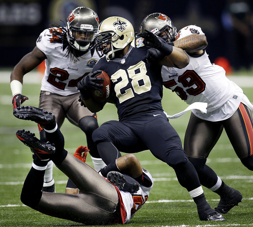 ADDS NAME OF PLAYER AT BOTTOM - New Orleans Saints running back Mark Ingram (28) carries as Tampa Bay Buccaneers middle linebacker Mason Foster (59), strong safety Mark Barron (24) cover and Saints Ronde Barber holds his foot in the first half of an NFL football game at the Mercedes-Benz Superdome in New Orleans, Sunday, Dec. 16, 2012. (AP Photo/Bill Haber)