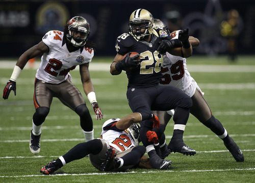 New Orleans Saints running back Mark Ingram (28) carries as Tampa Bay Buccaneers free safety Ronde Barber, below, and Tampa Bay Buccaneers middle linebacker Mason Foster (59) try to tackle in the first half of an NFL football game at the Mercedes-Benz Superdome in New Orleans, Sunday, Dec. 16, 2012. (AP Photo/Bill Haber)