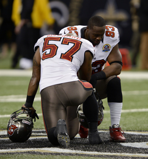 Tampa Bay Buccaneers outside linebacker Adam Hayward (57) and defensive tackle Gerald McCoy (93) pause for a moment of silence in memory of 20 children and six adults killed Friday in a shooting rampage at Sandy Hook Elementary School in Newtown, Conn., before an NFL football game against the New Orleans Saints at the Mercedes-Benz Superdome in New Orleans, Sunday, Dec. 16, 2012. (AP Photo/Bill Feig)