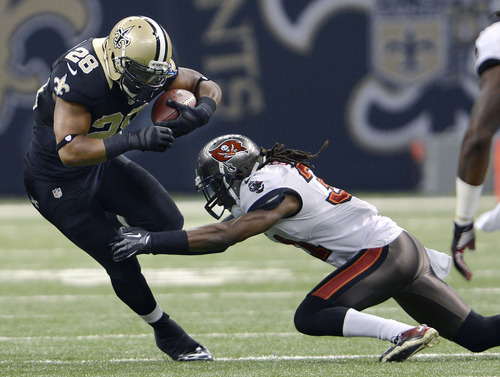 New Orleans Saints running back Mark Ingram (28) carries as Tampa Bay Buccaneers cornerback E.J. Biggers (31) tries to tackle in the first half of an NFL football game at the Mercedes-Benz Superdome in New Orleans, Sunday, Dec. 16, 2012. (AP Photo/Bill Feig)