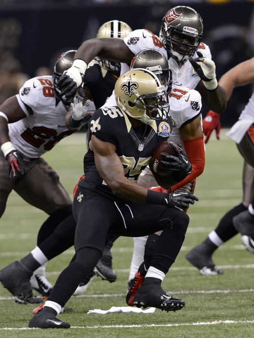 New Orleans Saints defensive back Rafael Bush (25) returns an interception past Tampa Bay Buccaneers wide receiver Tiquan Underwood (11) and running back D.J. Ware (28) in the first half of an NFL football game at the Mercedes-Benz Superdome in New Orleans, Sunday, Dec. 16, 2012. (AP Photo/Bill Feig)
