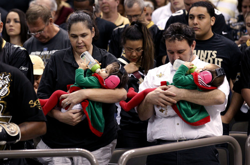 Fans pause during a moment of silence to honor 20 children and 6 adults killed Friday in a shooting rampage at Sandy Hook Elementary School in Newtown, Conn., in the first half of an NFL football game between the New Orleans Saints and the Tampa Bay Buccaneers at the Mercedes-Benz Superdome in New Orleans, Sunday, Dec. 16, 2012.  A gunman walked into Sandy Hook Elementary School in Newtown, Conn. Friday and opened fire, killing 26 people.  (AP Photo/Bill Haber)