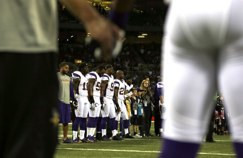 Members of the Minnesota Vikings hold hands during a moment of silence in honor of those killed Friday in shooting rampage at Sandy Hook Elementary School in Newtown, Conn., before the start of an NFL football game between the St. Louis Rams and the Minnesota Vikings Sunday, Dec. 16, 2012, in St. Louis.  A gunman walked into Sandy Hook Elementary School in Newtown, Conn. Friday and opened fire, killing 20 children and six adults.  (AP Photo/Jeff Roberson)
