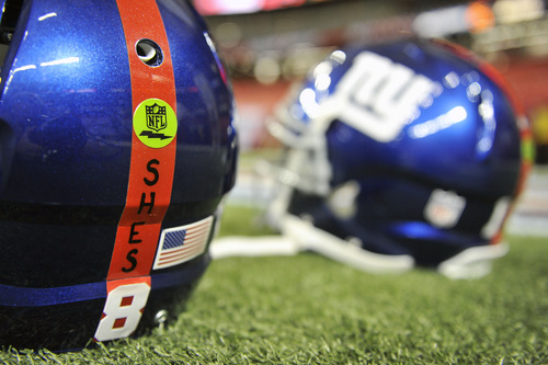 New York Giants helmets with a decal honoring the victims of the Sandy Hook Elementary School shooting rest on the turf before the first half of an NFL football game against the Atlanta Falcons, Sunday, Dec. 16, 2012, in Atlanta. A gunman walked into Sandy Hook Elementary School in Newtown Friday and opened fire, killing 26 people, including 20 children. (AP Photo/Rich Addicks)