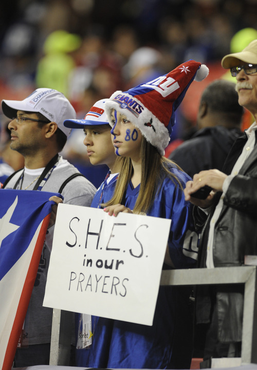Makayla Ferfecki, of Kentucky, hold a sign honoring the victims of the shooting at Sandy Hook Elementary School in Newtown, Ct., before the first half of an NFL football game between the Atlanta Falcons and the New York Giants, Sunday, Dec. 16, 2012, in Atlanta.  A gunman walked into Sandy Hook Elementary School in Newtown Friday and opened fire, killing 26 people, including 20 children. (AP Photo/Mike Stewart)