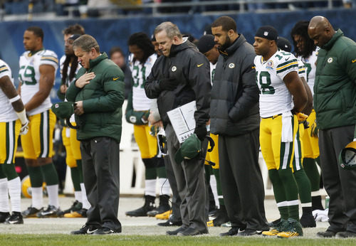 Green Bay Packers coach Mike McCarthy, center, stands with players and staff during a moment of silence for the victims of Friday's Connecticut elementary school shooting before an NFL football game against the Chicago Bears in Chicago, Sunday, Dec. 16, 2012.   A gunman walked into Sandy Hook Elementary School in Newtown, Conn. Friday and opened fire, killing 20 children and six adults.  (AP Photo/Charles Rex Arbogast)