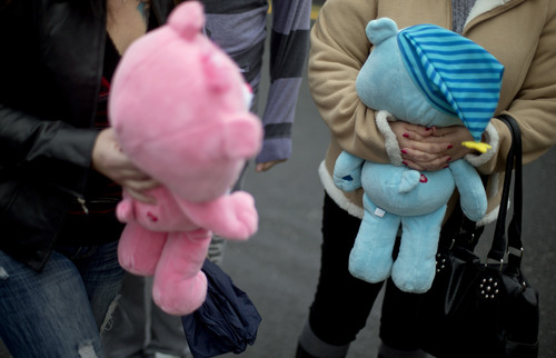 Natalie Zahra, of Vineland, N.J., right, and Amy Zimmerman, of Fairton, N.J., bring teddy bears to a sidewalk memorial for the Sandy Hook Elementary School shooting victims, Sunday, Dec. 16, 2012, in Newtown, Conn. A gunman walked into Sandy Hook Elementary School in Newtown Friday and opened fire, killing 26 people, including 20 children. (AP Photo/David Goldman)