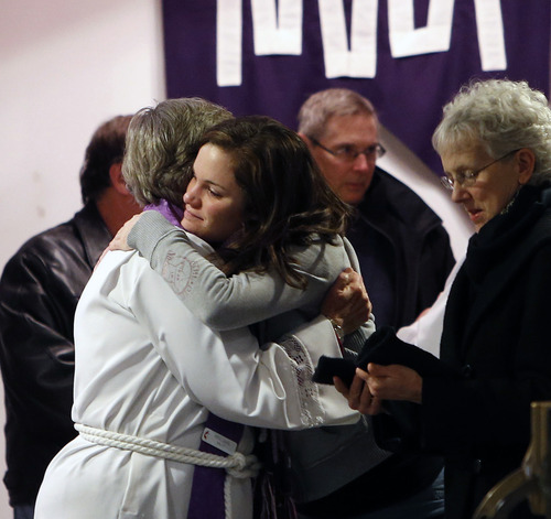 An attendee embraces a priest after attending a prayer service at Newtown United Methodist Church in the aftermath of a mass shooting at nearby Sandy Hook Elementary School, Friday, Dec. 14, 2012 in Newtown, Conn.  A gunman walked into the school Friday and opened fire, killing 26 people, including 20 children. (AP Photo/Jason DeCrow)