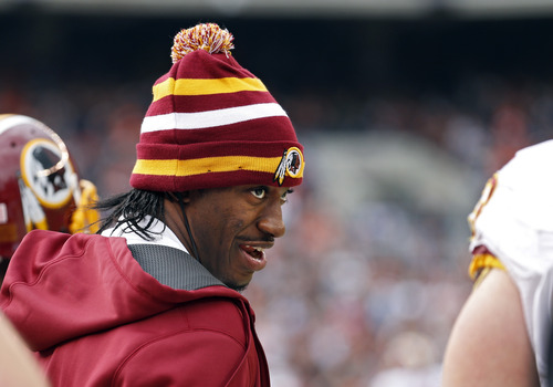 Injured Washington Redskins quarterback Robert Griffin III talks to teammates on the sidelines in the second quarter of an NFL football game against the Cleveland Browns in Cleveland, Sunday, Dec. 16, 2012. (AP Photo/Rick Osentoski)