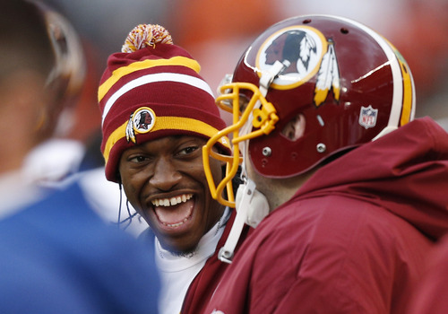 Injured Washington Redskins quarterback Robert Griffin III laughts with his teammates on the bench in the third quarter of an NFL football game against the Cleveland Browns in Cleveland, Sunday, Dec. 16, 2012. (AP Photo/Rick Osentoski)