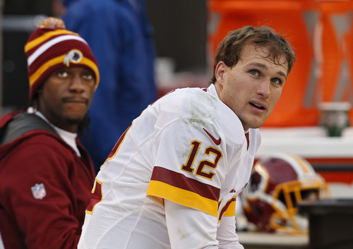 Cleveland Browns quarterback Colt McCoy (12) watches from the bench with Robert Griffin III in the fourth quarter o an NFL football game against the Cleveland Browns in Cleveland, Sunday, Dec. 16, 2012. (AP Photo/Rick Osentoski)