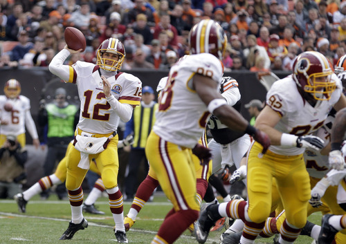 Washington Redskins quarterback Kirk Cousins (12) throws a screen pass to wide receiver Pierre Garcon in the second quarter of an NFL football game Sunday, Dec. 16, 2012, in Cleveland. (AP Photo/Tony Dejak)