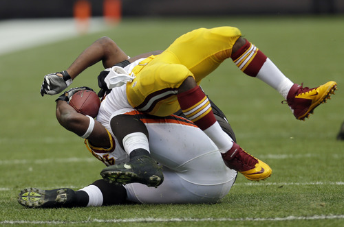 Washington Redskins running back Alfred Morris, top is brought down by Cleveland Browns linebacker L.J. Fort in the first quarter of an NFL football game Sunday, Dec. 16, 2012, in Cleveland. (AP Photo/Tony Dejak)
