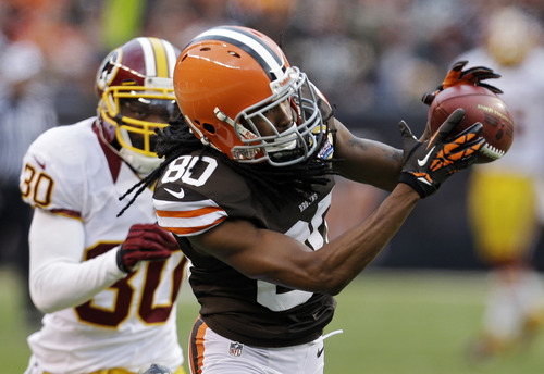 Cleveland Browns wide receiver Travis Benjamin (80) catches a pass in front of Washington Redskins cornerback DJ Johnson (30) and goes 69 yards for a touchdown in the fourth quarter of an NFL football game on Sunday, Dec. 16, 2012, in Cleveland. (AP Photo/Tony Dejak)