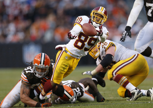 Washington Redskins wide receiver Santana Moss (89) fumbles after being hit by Cleveland Browns defensive end Jabaal Sheard (97) and linebacker D'Qwell Jackson (52) in the fourth quarter of an NFL football game in Cleveland, Sunday, Dec. 16, 2012. (AP Photo/Rick Osentoski)