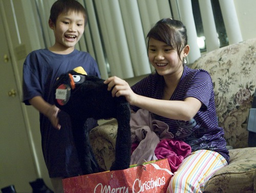 Keith Johnson  |  The Salt Lake Tribune Sunnay Bra, 10, left, watches as his sister Mu Kbaw, 14, unwraps an Angry Birds hat delivered by representatives from Catholic Community Services to the family of seven Burmese refugees at their home in South Salt Lake, December 12, 2012. The family arrived in Utah only a month ago.