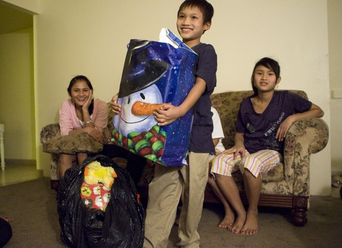 Keith Johnson  |  The Salt Lake Tribune Sunnay Bra, 10, holds a bag of gifts as his sisters Law Eh Dah, 17, and Mu Kbaw, 14, watch after representatives from Catholic Community Services delivered the presents to the family of seven Burmese refugees at their home in South Salt Lake, December 12, 2012. The family arrived in Utah only a month ago.