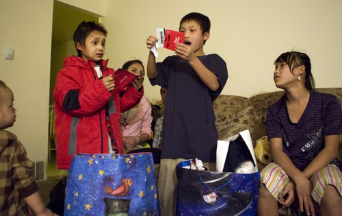 Keith Johnson  |  The Salt Lake Tribune Siblings Ehta Kpaw Say, 8, left, Mu Kbaw, 14, right, and Law Eh Dah, 17, rear, watch 10-year-old Sunnay Bra open an envelope containing a gift card from representatives from Catholic Community Services delivered the presents to the family of seven Burmese refugees at their home in South Salt Lake, December 12, 2012. The family arrived in Utah only a month ago.