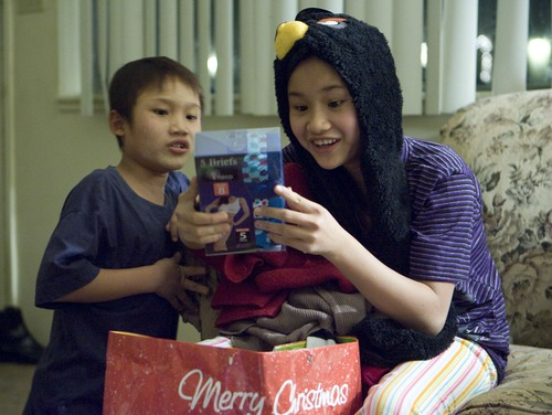 Keith Johnson  |  The Salt Lake Tribune Sunnay Bra, 10, left, watches as his sister Mu Kbaw, 14, unwraps gifts delivered by representatives from Catholic Community Services to the family of Burmese refugees at their home in South Salt Lake, December 12, 2012. The family arrived in Utah only a month ago.