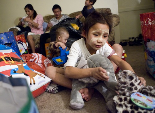 Keith Johnson  |  The Salt Lake Tribune Eight-year-old Ehta Kpaw Say unwraps gifts delivered by representatives from Catholic Community Services to the family of seven Burmese refugees at their home in South Salt Lake, December 12, 2012. The family arrived in Utah only a month ago.
