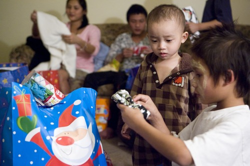 Keith Johnson  |  The Salt Lake Tribune Eighteeen-month-old Thyu Htoo watches his 8-year-old uncle Ehta Kpaw Say unwraps gifts delivered by representatives from Catholic Community Services to the family of Burmese refugees at their home in South Salt Lake, December 12, 2012. The family arrived in Utah only a month ago.