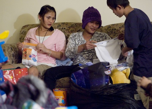 Keith Johnson |  The Salt Lake Tribune Law Eh Dah, 17, left, and Sunnay Bra, 10, right, watch as their brother Cha Kpaw Htoo unwraps gifts delivered by representatives from Catholic Community Services to the family of Burmese refugees at their home in South Salt Lake, December 12, 2012. The family arrived in Utah only a month ago.