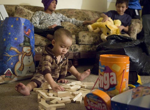 Keith Johnson  | The Salt Lake Tribune Eighteen-month-old Thyu Htoo plays with Jenga blocks after he and his family received gifts delivered by representatives from Catholic Community Services to the seven Burmese refugees at their home in South Salt Lake, December 12, 2012. The family arrived in Utah only a month ago.