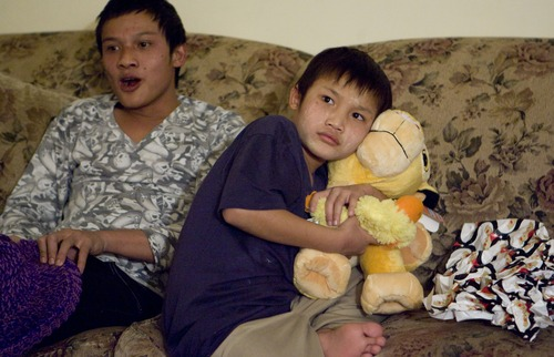 Keith Johnson  |  he Salt Lake Tribune Ten-year-old Sunnay Bra hugs a stuffed lion while sitting next to his brother Cha Kpaw Htoo after representatives from Catholic Community Services delivered gifts to the family of seven Burmese refugees at their home in South Salt Lake, December 12, 2012. The family arrived in Utah only a month ago.