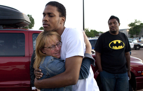 """FILE - In this Friday, July 20, 2012 file photo, Judy Goos, left, hugs her daughter's friend, Isaiah Bow, 20, an eyewitnesses, as Terrell Wallin, 20, right, looks on, outside Gateway High School where witnesses were brought for questioning after a gunman opened fire at the midnight premiere of the """"Dark Knight Rises"""" movie in Aurora, Colo. After fleeing the theater, Bow returned to find his girlfriend who turned out to be safe. """"Very stupid I know, But I didn't want to leave her in there,"""" says Bow. (AP Photo/Barry Gutierrez)"""