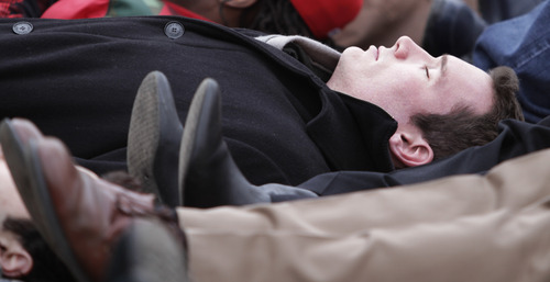 FILE - In this Jan. 17, 2011 file photo, Virginia Tech shooting survivor Colin Goddard participates in a lie-in during a rally protesting gun violence in Richmond, Va. For two years after a gunman shot four bullets into him, Goddard said he couldn't bear to listen to television reports about other shootings, or read about them. It brought him back instantly to that day - April 16, 2007 - when he lay on the floor of classroom 211, blood dripping from his shoulder and leg as he wondered if he would survive. (AP Photo/Steve Helber, File)