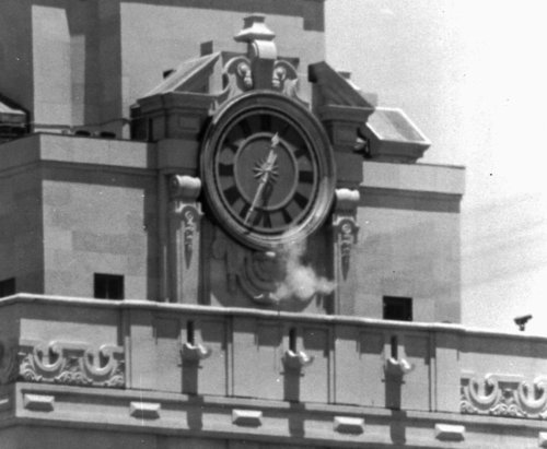 """FILE - In this Aug. 1, 1966 file photo, smoke rises from a sniper's gun as he fires from the tower of the University of Texas administration building in Austin, Texas at people below. Grant Duwe, a criminologist with the Minnesota Department of Corrections, says, """"Mass shootings provoke instant debates about violence and guns and mental health and that's been the case since Charles Whitman climbed the tower at the University of Texas in 1966."""" The engineering student and former Marine killed 13 people and an unborn child and wounded 32 others in the shooting. (AP Photo/File)"""