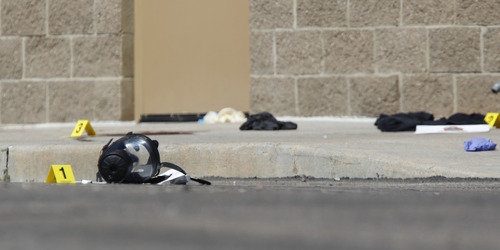 FILE - In this Friday, July 20, 2012 file photo, yellow markers sit next to evidence, including a gas mask, as police investigate the scene outside the Century 16 movie theater east of the Aurora Mall in Aurora, Colo. after a gunman in the theater killed 12 people. (AP Photo/David Zalubowski)
