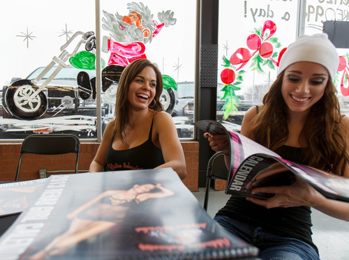 Trent Nelson  |  The Salt Lake Tribune Models Jennifer Comer and Liz Phelps share a laugh during a signing party for a charity calendar put out by Addictive Behavior Motor Works in Salt Lake City, Saturday December 15, 2012.