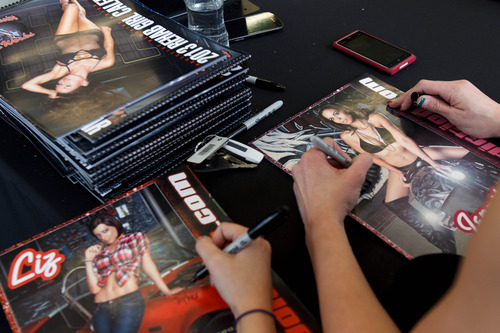 Trent Nelson  |  The Salt Lake Tribune Jennifer Comer signs her photograph in a charity calendar put out by Addictive Behavior Motor Works in Salt Lake City, Saturday December 15, 2012.