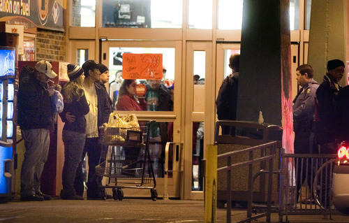 Bystanders watch as Topeka police investigate at the scene of a shooting outside a grocery store in Topeka, Kan., Sunday, Dec. 16, 2012. Two Kansas police officers were shot outside the store on Sunday while responding to a report of a suspicious vehicle and died later at a hospital, authorities said. (AP Photo/The Topeka Capital Journal, Thad Allton)