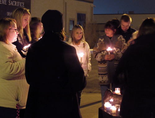 People gather for a small candlelight vigil on Sunday, Dec. 16, 2012, at the Law Enforcement Center in Topeka, Kan. Two Kansas police officers were shot outside the store on Sunday while responding to a report of a suspicious vehicle and died later at a hospital, authorities said. (AP Photo/The Topeka Capital Journal, John Hanna)