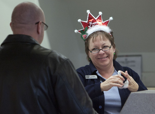 Steve Griffin | The Salt Lake Tribune   Lynn Sasaki, a post worker for 15 years, laughs as she tries to remove tape from her fingers as she helps a customer at the Post Office on 2100 south and Redwood Road in Salt Lake City, Utah Monday December 17, 2012.  Utahns are expected to mail nearly 2 million cards and packages on Monday, Dec. 17, making it the busiest mailing day of the year. More than 650 million cards and packages are expected nationwide. Fully staffed Post Offices will greet customers, and postal managers will be in lobbies to answer questions and provide assistance.