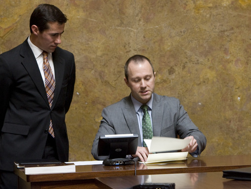 Kim Raff  |  The Salt Lake Tribune (left) Justin Lee, deputy director of elections, listens as Taylor Morgan, election specialist, reads aloud results of Electoral College ballots for president of the United States during Utah's vote in the old Supreme Court chambers at the State Capitol in Salt Lake City on Monday, Dec. 17, 2012.