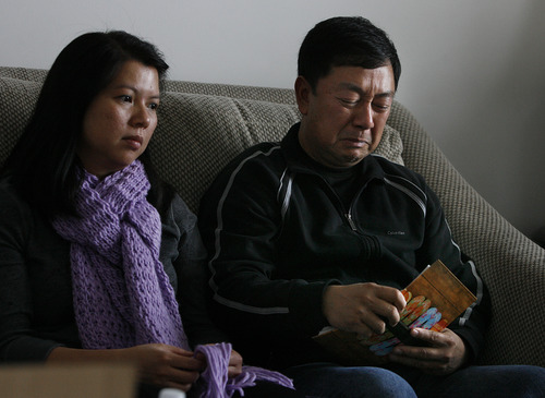 Scott Sommerdorf  |  The Salt Lake Tribune               Nhuan Phan, right, father of David Phan, cries as he looks through a family photo album containing photos of their son David. David's mother, Phuong Tran is at left.  The Phan family spoke out for first time, Saturday, December 15, 2012 about why David committed suicide on Nov. 29 at Bennion Junior High.
