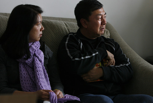 Scott Sommerdorf     The Salt Lake Tribune               Nhuan Phan, right, father of David Phan, cries and clutches to his chest a family photo album containing photos of their son David. David's mother, Phuong Tran is at left.