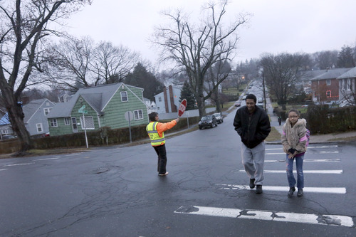 Rudy McCarley, left, walks his daughter Zarina to the Morris Street Elementary School, Monday, Dec. 17, 2012 in Danbury, Conn. Teachers and parents across the country were wrestling with how best to quell children's fears about returning to school for the first time since the killings at Sandy Hook Elementary School in Newtown, Conn. (AP Photo/Mary Altaffer)