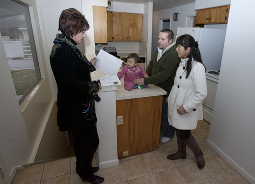 Steve Griffin | The Salt Lake Tribune   Realtor Donna Pozzuoli, left, shows Matt and Megumi Garriott and their daughter, Mia Grace,  a 2200 square foot home in Salt Lake City, Utah Tuesday December 18, 2012. Pozzuoli says she may have missed six sales and $12,000 in commissions because some of her clients are nervous that the fiscal cliff deadline will pass without an agreement on how to reduce the budget deficit and nation's debt. Some clients feel their taxes will rise; others worry that their employers might need to lay them off.