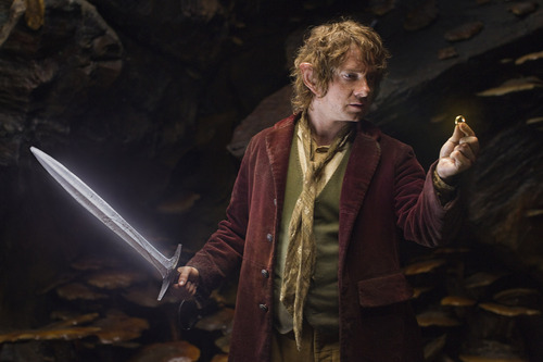 """Martin Freeman as the Hobbit Bilbo Baggins with his sword, Sting, finds a small ring in Gollum's cave in the fantasy adventure  """"The Hobbit: An Unexpected Journey."""""""